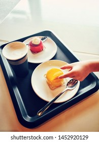 Closeup of kids child hand trying to steal tasty cakes from plate on tray. Impatient person taking food dessert on dish. Tasty delicious pastry with coffee cup in cafeteria cafe.