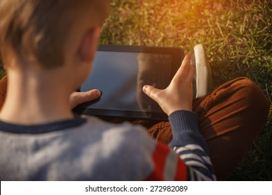 Close-up of kid's hands close up holding  digital tablet for playing and education
