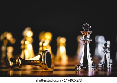 Closeup king chess piece defeated enemy or trade competitor by checkmate at end of chessboard game. Businessman moving chess to success competition by hand. Leadership and strategy management