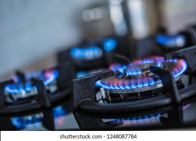 Close-up kitchen stove cook with blue flames burning.