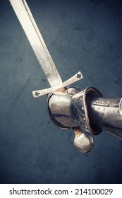 closeup of knight's hand in armor gloves holding two-handed sword