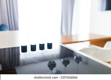 Closeup of knobs on modern luxury electric cook stove top cooktop with glass reflection and circles background in empty home