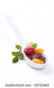 Closeup of a la carte spoon filled with delicious chocolate souffle  served with fresh raspberry, kumquat and mint