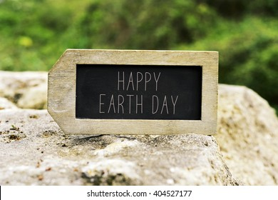 closeup of a label-shaped chalkboard with the text happy earth day on a rock with a landscape in the background
