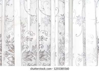 Closeup of lace white window curtains blinds in bright room interior indoors with floral pattern design abstract decoration