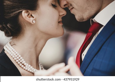 A closeup of lady in pearls and man in red tie leaning to each other