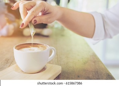 Closeup of lady pouring sugar while preparing hot coffee cup