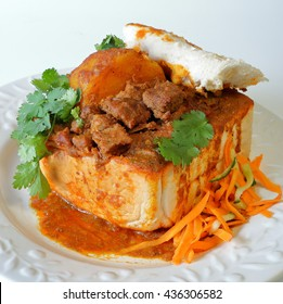 """Closeup of lamb """"bunny chow"""" - the popular, Indian fast food cuisine which originated in South Africa, with carrot salad"""