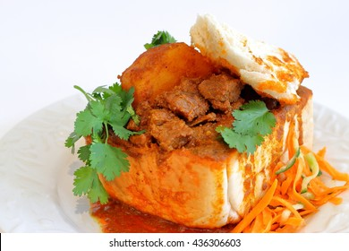 """Closeup of lamb """"bunny chow"""" - the popular, Indian fast food cuisine which originated in South Africa"""