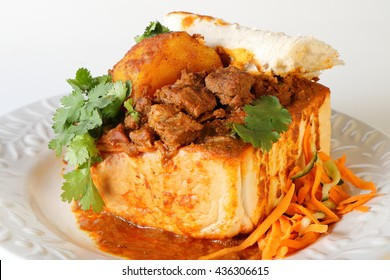 "Closeup of lamb ""bunny chow"" - the popular, Indian fast food cuisine which originated in South Africa, with carrot salad"