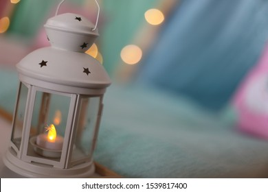 A closeup of a lantern with a tealight candle and a bokeh effect of fairy lights with teepees set up in the background.