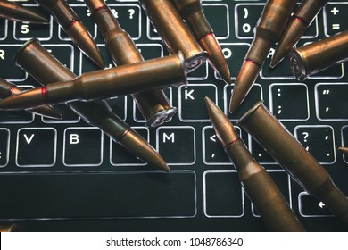 Closeup of laptop computer keyboard, and gun bullets, representing the concept of cyber attacks, Journalism, terrorism, support for terrorists, click enter