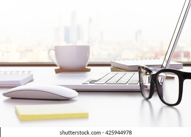 Closeup of laptop, glasses, coffee cup and other items on white desktop with blurry city in the background