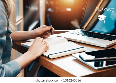 Close-up of laptop with inscription on screen - e-learning and picture of square academic cap. Girl sits at table, takes notes in notebook, holds smartphone. Online education, e-learning, webinar.
