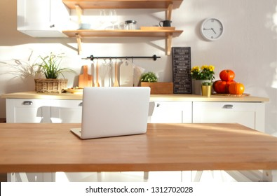 Closeup of laptop on kitchen counter. Kitchen on background