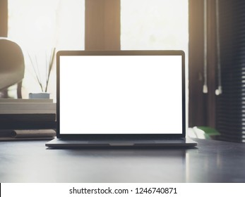 Closeup of laptop with white blank screen on wood table in working office background