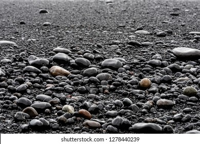 Closeup of large black volcanic stones or pebbles on sand beach in Reynisfjara, Iceland with shore and shiny wet rocks