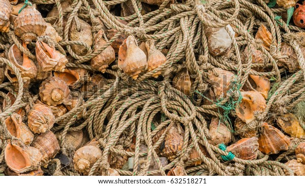 Closeup of large collection of fishing nets made of rope and seashells
