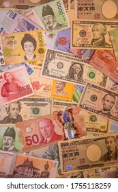 A closeup of a large colorful pile of U.S., Canadian, Malaysian, and Taiwan banknotes.