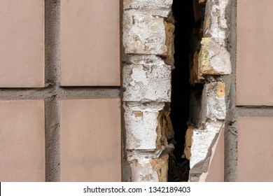 Close-up of large crack on a tiled wall, selective focus. old broken wall with a deep crack, the building must be renovated