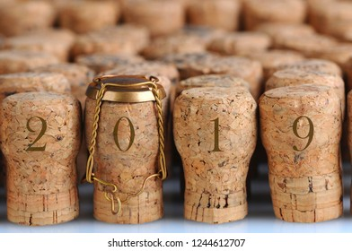 Closeup of a large group of Champagne corks, with the year 2019. Selective focus on the front row. One cork has the metal cage.