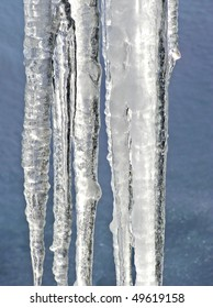 Close-up of large icicles melting showing every details of the light relfected by the ice with blue crusted snow as background
