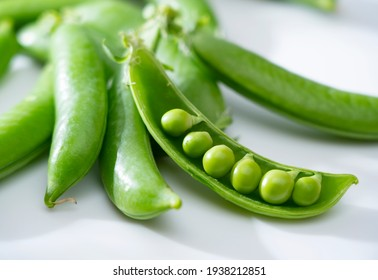 Close-up of a large number of snap peas on a white background