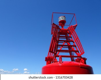 Closeup of large red harbour buoy against blue sky background Wellington New Zealand