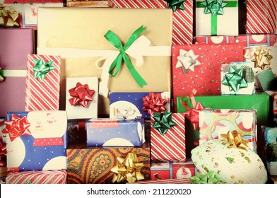 Closeup of a large stack of wrapped Christmas presents of varying sizes and shapes