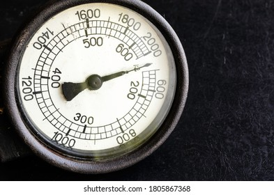 Close-up of large tachometer dial. Old mechanical measuring instrument on a black background. Copy space. Selective focus.
