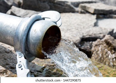 close-up of a large water or sewage pipe with a stream of water or waste gushing onto rocks by a bay