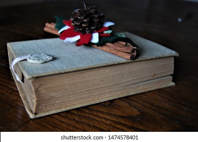 Closeup lateral view of an old book with beige cloth cover a bookmark shaped like a heart and a Christmas decoration of cinnamon a small green red white garland  and a cone over it laying on wood