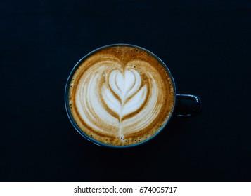 closeup latte art coffee in black cup on black table