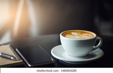 Closeup latte art coffee in white cup with smartphone and notebook on black table. Vintage color tone