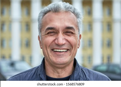 Closeup laughing face of an elderly businessman, civil servant, doctor or television presenter. Portrait of a joyful caucasian man over fifty years, with short gray hair outdoors, near public building
