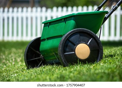 Closeup of lawn spreader in grass yard used for applying grass seed, fertilizer, herbicides, pesticides to kill weeds, white picket fence in background, lawn maintenance program, healthy lawn care