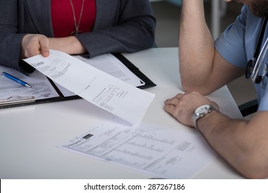 Close-up of lawyer giving the summons to young doctor