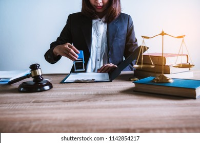 Close-up of lawyer working hand holding automatic stamp important contract papers documents in office. lawyer and law ,judiciary and legislature courtroom legal concept.