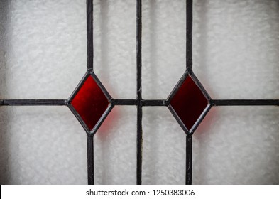 Close-up of leaded stained glass window with red diamond patterns