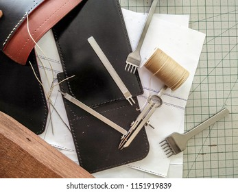 Closeup leather work area with some tools such as leather sheets, cutting mat, hole puncher, needle, thread and divider compass