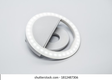 Close-up LED selfie circular ring light lamp on white background. Clip-on flash light camera phone for taking selfie photos and videos. Compact and lightweight device for bloggers and vloggers.