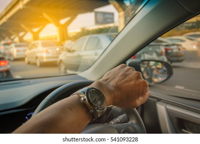 Closeup left hand driving on traffic jam background, Business Concept