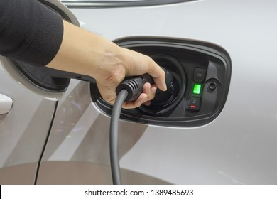 Close-up left hands men who are fueling a new vehicle electrification via rechargeable electricity machine, Electric cars are a new innovation in the future, built to replace cars powered by oil.