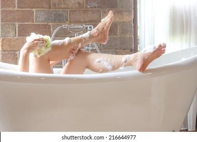 closeup leg women taking a shower in a bathtub