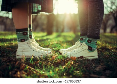 Closeup of legs of a boy and a girl in sneakers on green grass on a background sunset. A pair of teenagers during a romantic walk. The concept of a first date.