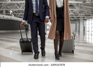 Close-up of legs of businessman and businesswoman are going to departure area with luggage. They are having business trip
