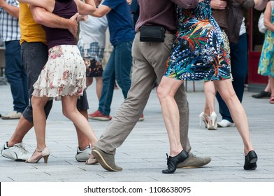 closeup of legs of couples of tango dancers in the street