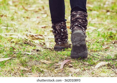 Closeup of legs with dark pants and shoes walking on grassy forest surface.