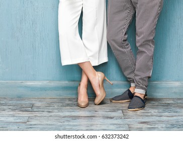 Closeup of legs of a guy and a girl standing on the floor on a blue background