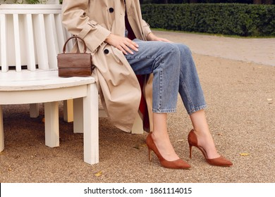 Closeup legs high heels, woman in beige coat and blue jeans with brown leather bag. Fashion street autumn outfit